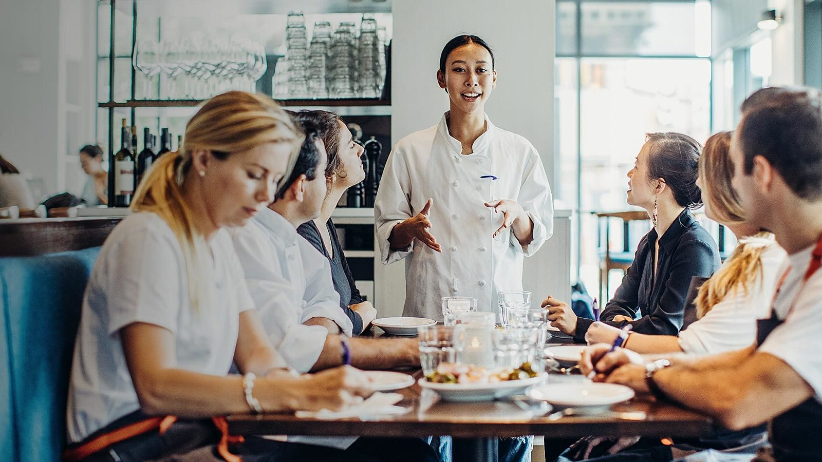 A chef leads a pre-shift meeting about an employee incentive program.