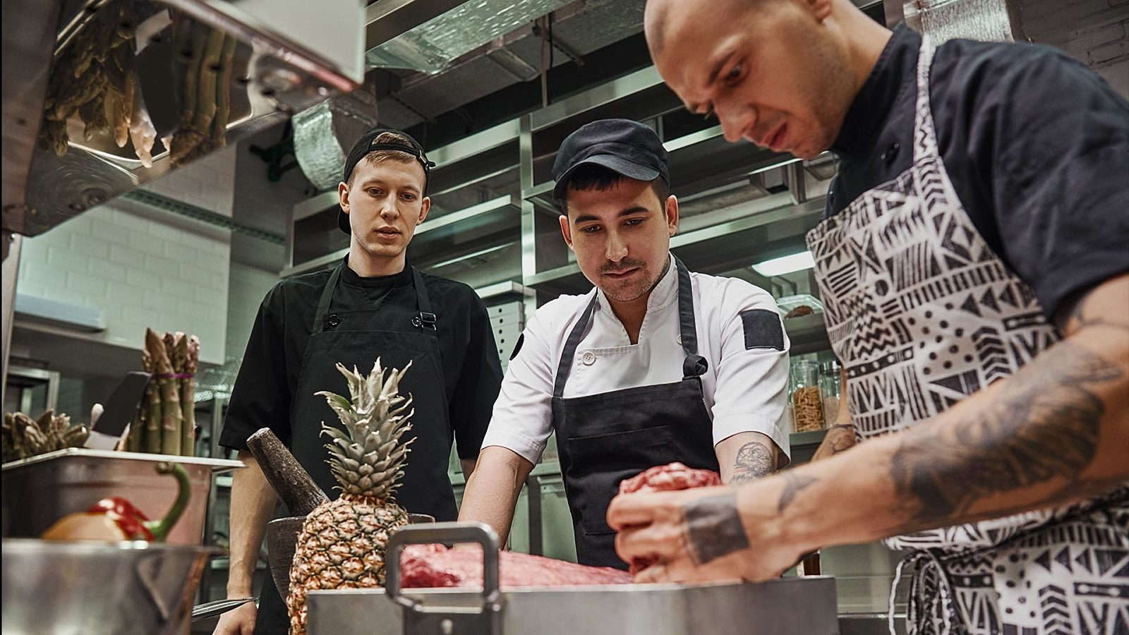 A cook showing another cook how to train restaurant employees, holding some ingredients.
