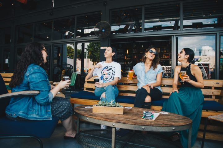 Four women chatting while sitting on bench 1267697