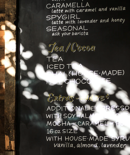 A large wooden-framed chalk menu for a cafe, showing specialty coffee drinks, tea and cocoa options, and extras.