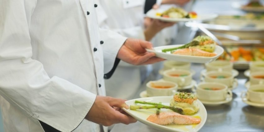 Chef Holding Salmon Dishes Standing In A Row With Colleagues 582657 Edited