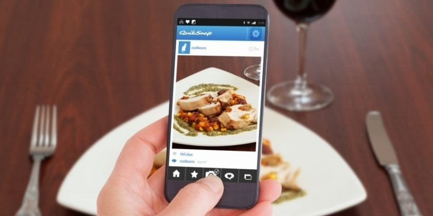 Female Hand Holding A Smartphone Against High Angle View Of Delicious Chicken Dish With Salsa 796619 Edited