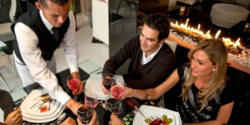 Group Of People At A Restaurat Having Dinner Being Served By A Waiter 879074 Edited