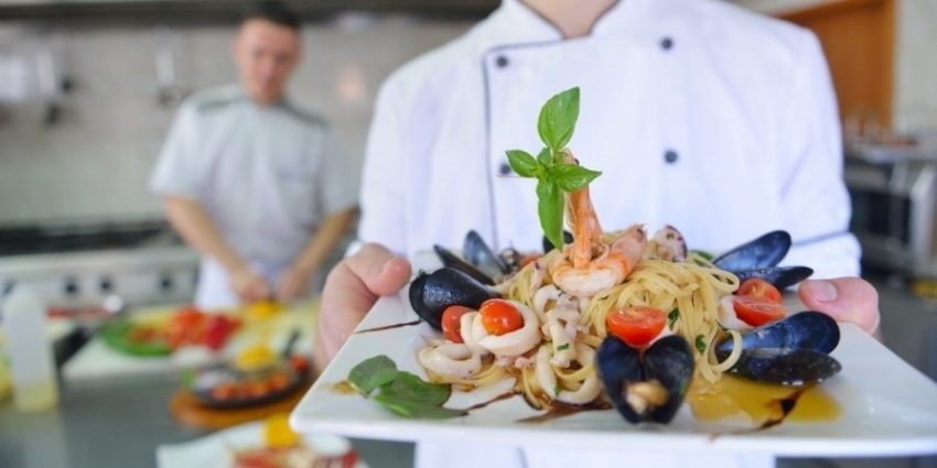 Handsome Chef Dressed In White Uniform Decorating Pasta Salad And Seafood Fish In Modern Kitchen 768706 Edited
