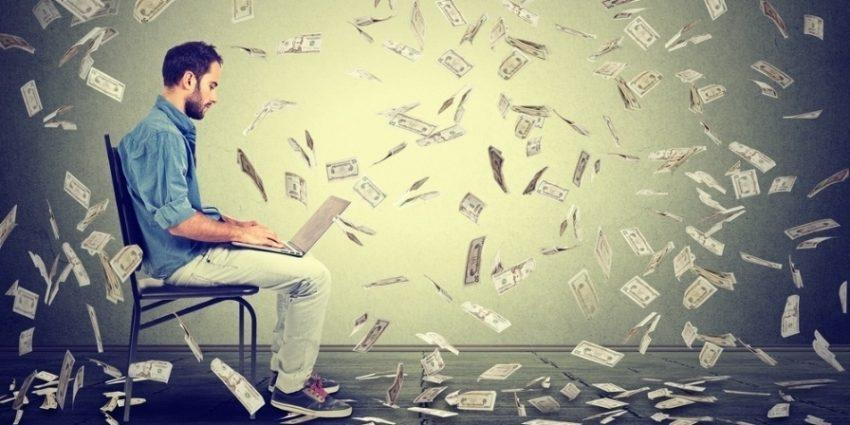 Young Man Using A Laptop Building Online Business Making Dollar Bills Cash Falling Down  Beginner It Entrepreneur Under Money Rain  Success Economy Concept  077026 Edited