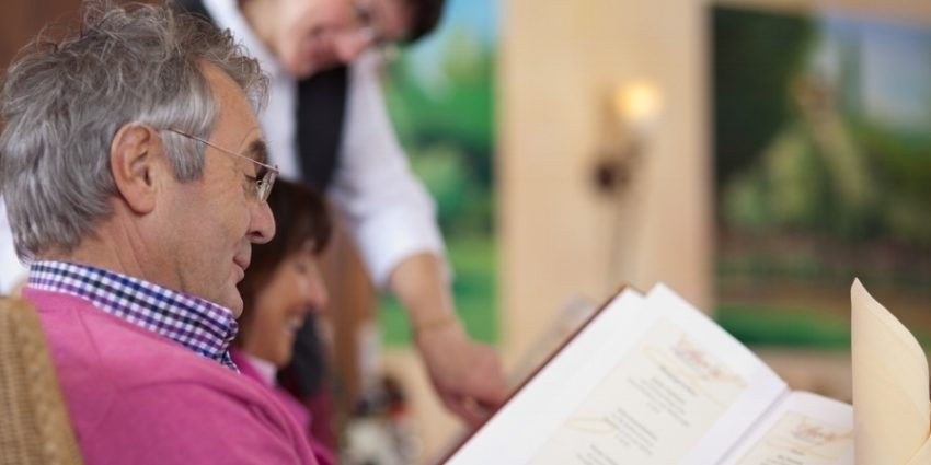 Smiling Guest In Restaurant Reading The Menu With Waitress In Background 677453 Edited