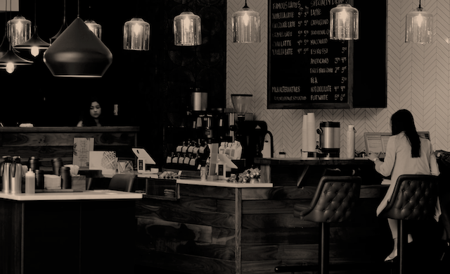 a black and white image of a cafe with seven overhead hanging lightbulbs with large glass covers