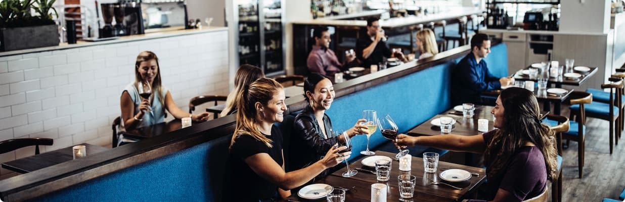 Restaurant party enjoying glasses of wine before their meal