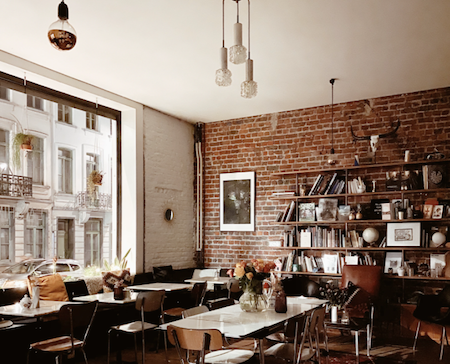 A warm restaurant with a brick wall and white ceiling, with a large shelving unit against the wall containing photos, tons of books, and other trinkets.