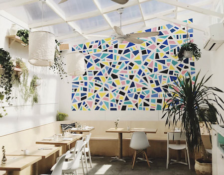 a bright restaurant with a glass ceiling, white walls, plants all over, and one wall covered in a geometric, colorful pattern.