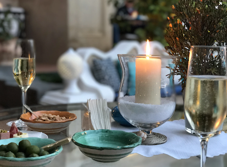 A beautiful tablescape including a wide glass candleholder, turquoise and terra cotta bowls of snacks, some green branches, and two champagne flutes.