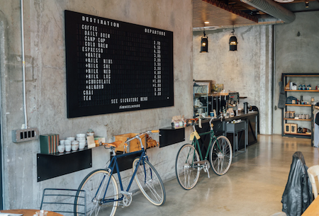 A bike-themed cafe with a large black menu up on the wall, grey industrial finishes, and simple shelves with coffee fixins and decor.